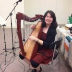Kids' short story author Deirdre McCarthy playing harp at an Irish music festival