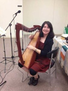 Kids' short story author Deirdre McCarthy playing harp at an Irish music festival