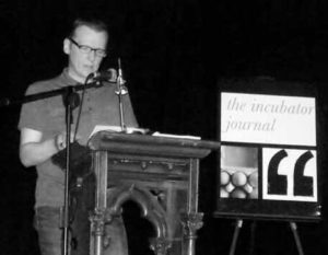 "A> Joseph Black author on a podium with ""the incubator journal"" on a sign beside hime"