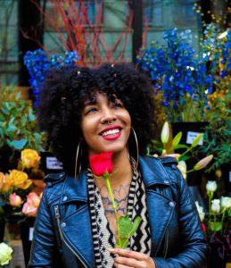 Simone Stephens author photo - holding a red tulip